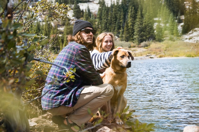 couple and dog on a hike outdoors